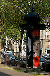 Old street urinal used as advertising hoarding.Paris, France.