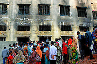 Workers stand outside the destroyed factory after the blaze. At least 112 people died, and more than 100 were injured at a fire at the Tazreen Fashions textile factory in Dhaka. Bangladesh's garment industry has a notoriously bad fire safety record; if the right precautions had been taken, the fire could have been prevented.