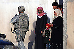 An Iraqi man and his family stand aside as a U.S. soldier passes by them on patrol in Mosul, Iraq. Soldiers from Company A, 1st Battalion, 8th Infantry Regiment are establishing combat outposts in the eastern half of the city,  a stronghold for insurgents. Many residents of Mosul are cordial with U.S. troops, but they also maintain their distance, reflecting a deep ambivalence about being squeezed between U.S. and Iraqi government forces and the various insurgent groups who remain powerful in the city. Feb. 19, 2008. DREW BROWN/STARS AND STRIPES