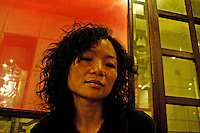 Returnee Chinese woman - working in Shanghai, originally from Guangdong, but with a European nationality - waiting for a restaurant table.