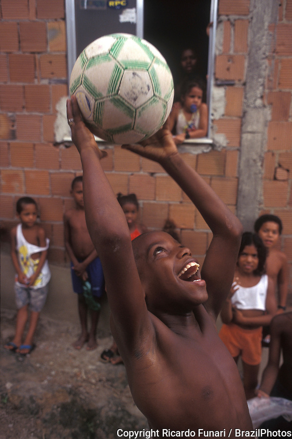Daily life in Rio de Janeiro favela, black boy laughs and have fun with his ball - Morro da Mangueira.