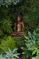 A hand-carved Buddha sits serenely amongst the bamboo in a quiet corner of the garden