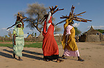 Fatna (right) brings home wood that she and some neighbors have harvested from outside a camp for internally displaced persons outside Kubum, in South Darfur, where international agencies are providing water, sanitation and other emergency services.