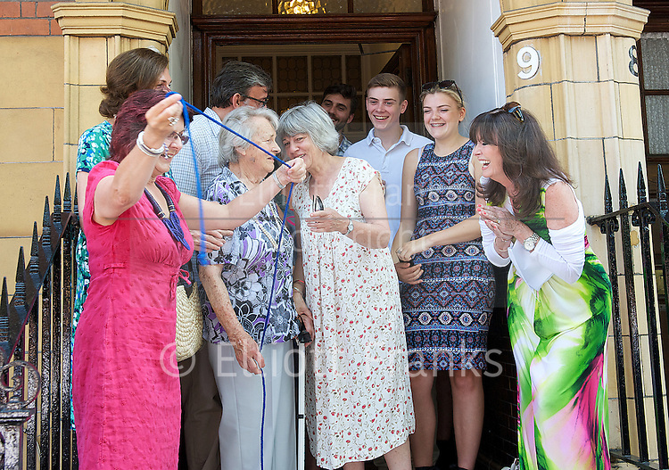 Eric Sykes <br /> Blue plaque unveiling <br /> by the Heritage Foundation<br /> at 9 Orme Court, Bayswater, London, Great Britain <br /> <br /> 7th July 2013 <br /> <br /> <br /> with his wife Edith Sykes  (Milbrandt)<br /> <br /> daughters<br /> <br /> Julie (wearing pink)<br /> Kathy (wearing white/flowery dress)<br /> Susan (wearing the green dress)<br /> <br /> and his son <br /> <br /> David<br /> <br /> <br /> also with his grandchildren <br /> <br /> also photographed:<br /> <br /> Bill Kenwright <br /> West End theatre producer and film producer<br /> <br /> Pamela Cundell<br /> who played Mrs Fox in dad's Army <br /> <br /> Frank Williams who played <br /> The Reverend Timothy Farthing <br /> in Dad's Army <br /> <br /> Jeffrey Holland<br /> <br /> <br /> Photograph by Elliott Franks