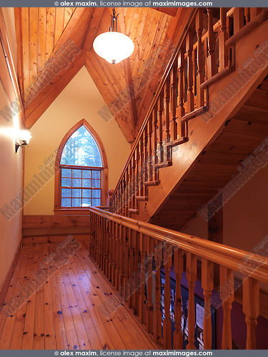 Timber-frame cottage style Canadian country house hall interior with a wooden staircase and a gothic arched cathedral window, Muskoka, Ontario, Canada