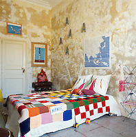 This teenager's bedroom has a simple, rustic feel with a distressed finish on the walls and a flagstone floor. The bed has a colourful knitted patchwork blanket