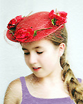 Young girl in vintage red straw hat with silk flowers, from shoulders up, close-up portrait (model released)