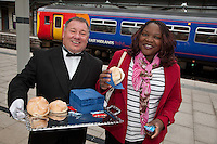 Pictured handing out free bacon butties to promote East Midlands Trains complimentary breakfast for First Class passengers is singing butler Alberto and Derby passenger Vimbai Gori