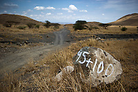 A stone marker on the road between Arusha and Loliondo, left behind by surveyers. The government of Tanzania is planning to turn this dirt track into a highway that will connect isolated communities and bring much needed development to the marginalised Masaai. However, the highway will cut straight through the Serengeti National Park, a World Heritage Site, disrupting animal migration, which would have disastrous consequences for the entire park ecosystem.