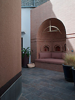Tucked away in the gardens is an outdoor niche clad in skinny Italian bricks. The brass light was custom-made to Christopher Hall's design.  The ceramic flooring was sourced locally