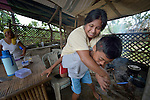 Christina Balitor gets a ride from her son in Estancia, in the Philippines province of Iloilo. A survivor of childhood polio, she cannot walk on her own. She washes laundry to earn a meager living. Her wheelchair broke six years before and she has been unable to afford a new one. Her house was washed away by Typhoon Haiyan, known locally as Yolanda, in November 2013. Balitor now lives with her sister.