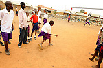 A Kenyan soccer player shooting on goal with his friends watching,  near Likoni, Kenya.   This dirt field soccer field is backed by a town trash dump