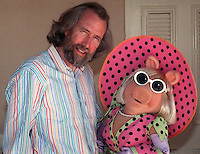 "Miss Piggy  and companion Jim Henson take a break from reporters in May 1989 in Los Angeles to talk about ""The Jim Henson Hour,"" a magazine style show to be aired by NBC that mixes half hour ""The Storyteller"" dramatic pieces , ""Miss Piggy's Hollywood,"" and  Muppet creatures in various pieces. ""I think we've always pushed puppetry to the limits,"" says Henson. ""Now we're pushing new technologies to the limit. (Photo by Alan Greth)"