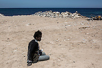 An illegal sub-Saharan migrant is pictured downcast on the Tajoura shore after having been arrested in the Mediterranean Sea by the Libyan coastguard in the west of Libya.