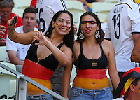 Two German supporters with the national flag painted on their stomachs cheer their side on