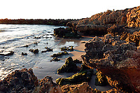A small bay created by the erosion of sand during winter storms.