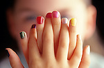 Young girl showing off her newly painted multicolored finger nails