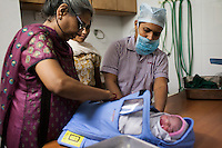Paediatrician and neonatal specialist Anita Kothiala (left) is assisted by nurse Sejal Parmar (right), as she wraps a new born baby in a thermal wrap after a surrogate went into labor and gave birth unexpectedly in the Akanksha Infertility Center in Anand, Gujarat, India on 12th December 2012.  Photo by Suzanne Lee / Marie-Claire France