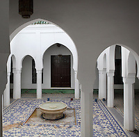 Ablutions room of the Mausoleum of Moulay Idriss I, open only to non-muslims, with its central fountain, tiled floor and horseshoe arch colonnade, Moulay Idriss, Meknes-Tafilalet, Northern Morocco. The mausoleum was rebuilt by Moulay Ismail, 1672-1727, in the 17th century and is the site of an important moussem or pilgrimage festival each summer. The town was founded by Moulay Idriss I, who arrived in 789 AD and ruled until 791, bringing Islam to Morocco and founding the Idrisid Dynasty. His body was moved to a tomb in the mausoleum. Picture by Manuel Cohen