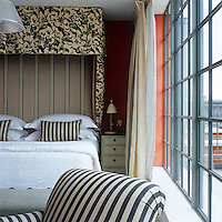 Constrasting black and white stripes and florals on the headboard and bedding are set against orange walls in a hotel bedroom in London