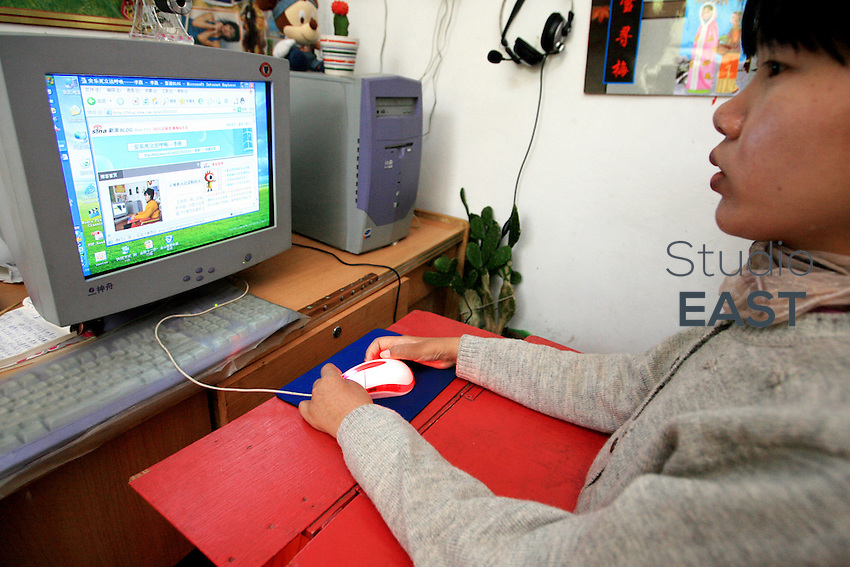 Li Yan sits in front of her computer in her home in Yinchuan, Ningxia Province, China, on May 7, 2007. Li Yan spends up to 10 hours per day in front of her computer, producing colourful paintings and writing her blog (on screen). 28-year-old Li Yan suffers from motor neuron disease also known as amyotrophic lateral sclerosis (or ALS), the same illness that has thereotical physicist Stephen Hawking. Li Yan asked China's National People's Congress (NPC) to consider a draft on euthanasia. Photo by Lucas Schifres/Pictobank