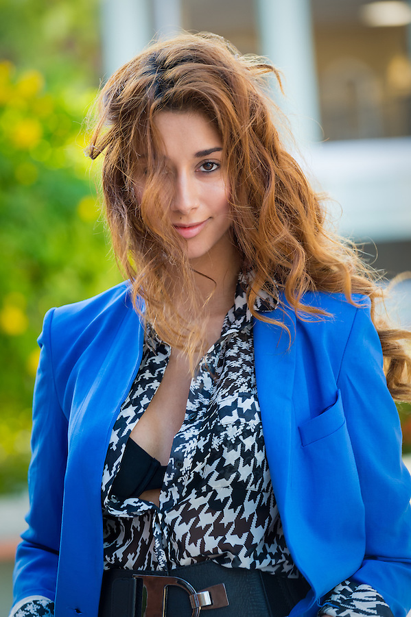 Beautiful elegant young woman dressed in trendy and stylish blouse standing outdoors looking at the camera smiling and long curly brunette hair