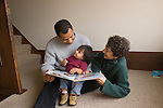 Berkeley CA Adopted Guatemalan girl, eighteen-months-old, in loving interaction with Cuban father while parents read book to her  MR