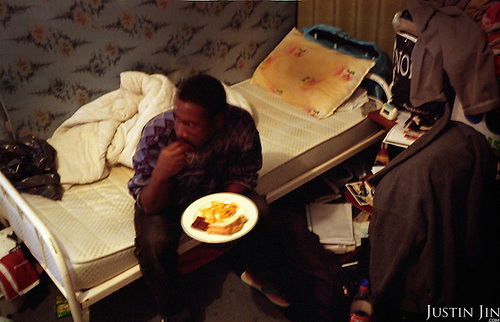 An illegal immigrants from Niger consumes his dinner at home in Amsterdam Bijlmer area. The immigrant, Johnny, was a high-school teacher back home. .Picture taken 2002 by Justin Jin. ..