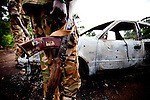 South Sudan soilders with the SPLA inspect a car that was ambushed by the LRA and burnt killing three civilians traveling from Yambio to Tambura in Western Equatoria.