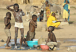 Children in the Aradib Camp for internally displaced persons outside the village of Goz Amer, Chad, taking a bath near a community well. Some 28,000 people live in precarious conditions in this camp. More than 180,000 residents of eastern Chad have been displaced by violence spilling over from neighboring Darfur, inter-ethnic conflict, and fighting between rebels and the Chadian government.