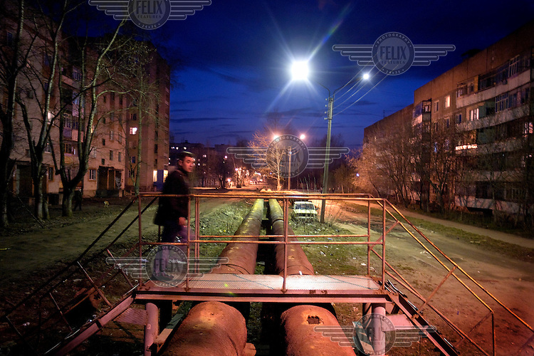 A man walks across an exposed gas pipe in a housing estate in the city of Ivanovo.