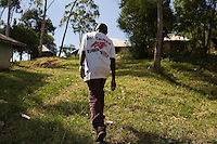 Clinton walking home to his grandparent's house. Clinton has  been recieving medical care for HIV  since 2003. He has yet to begin  ARVs.  His parents died within six months of each other from AIDS. They refused to be tested and never sought treatment.