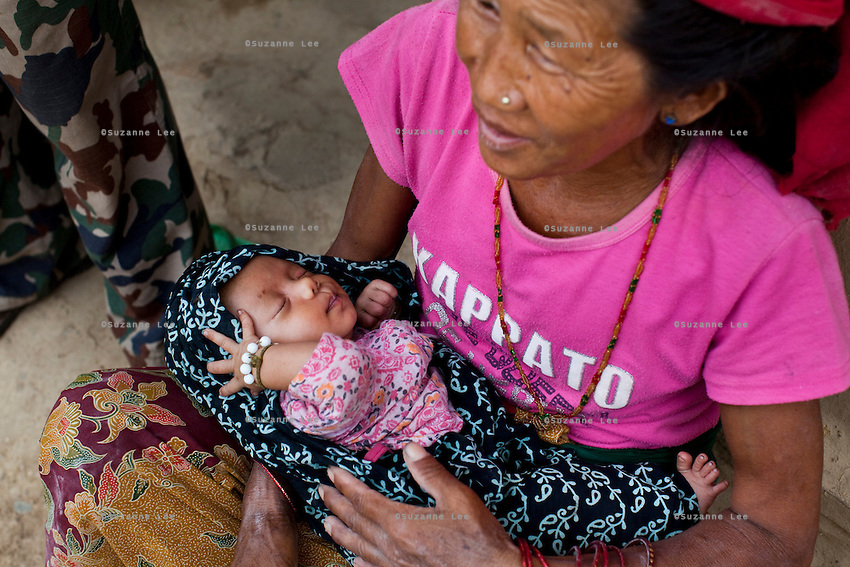 19 year old Nisha Darlami's mother carries her 1 month old baby girl, Bushpa in Kalyan Village, Surkhet district, Western Nepal, on 30th June 2012. Nisha eloped with her step nephew when she was 13 but the couple used contraceptives for the next 6 years to delay pregnancy until she turned 18. In Surkhet, StC partners with Safer Society, a local NGO which advocates for child rights and against child marriage. Photo by Suzanne Lee for Save The Children UK