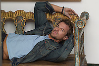 good looking All American man reclining on a wooden bench at home