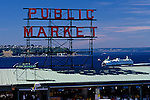 Pike Place Market sign on a sunny day with Washington State ferry on Elliot Bay, Seattle, Washington State USA