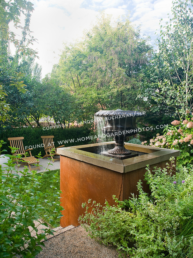A water feature set among lush mixed beds serves as a focal point for the seating area featuring teak deck chairs in this multi-levelled Seattle back yard. Design by Scot Eckley, Inc.