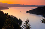 Idaho, North, Coeur d'Alene. An after sunset view over the north end of Lake Coeur d'Alene from Mineral ridge, between Beauty and Wolf Lodge Bays with motorboat and wake.