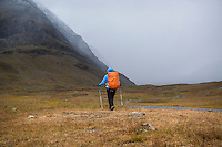 Female hiker watches as autumn snow storm approaches in Tjäktjavagge on Kungsleden trail, Lappland, Sweden