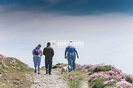 A family and their dog walk along a path on East Pentire Headland in Newquay, Cornwall.