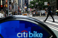 New York, USA. 28 May 2014. A woman walks next to a Citi bike during the one year anniversary in New York. Photo by Eduardo Munoz Alvarez/VIEWpress