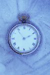 Classic pocket or fob watch with white face and black Roman numerals embedded in ice