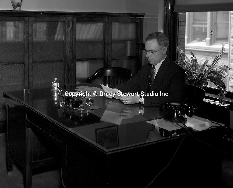 Pittsburgh PA: Administrator reading documents in his office at Duquesne University - 1932