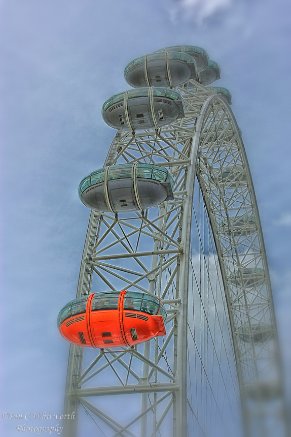 Looking up at the large ovoidal passenger capsules on the London Eye, with a red one in the foreground.