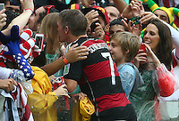 Bastian Schweinsteiger of Germany climbs into the stands at full time to kiss a woman believed to be his partner Sarah Brandner