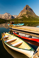 Canoes and row boats on the dock of Swiftcurrent Lodge at Swiftcurrent Lake and Grinnell Point - Many Glacier area, Glacier National Park, Montana.
