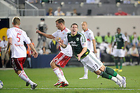 Kenny Cooper (33) of the Portland Timbers goes down under pressure from Teemu Tainio (2) of the New York Red Bulls. The New York Red Bulls defeated the Portland Timbers 2-0 during a Major League Soccer (MLS) match at Red Bull Arena in Harrison, NJ, on September 24, 2011.