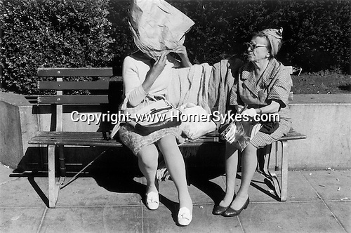 Two older women chatting in a  downtown park, one has made a bonnet  from a brown paper bag to shield her self from the sun. San Francisco, California. 1971