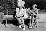SAN FRANCISCO, CALIFORNIA - USA 1971: TWO OLDER  WOMEN SITTING ON A BENCH IN A DOWNTOWN PARK ONE MAKES A BONNETT  FROM A PAPER BAG TO SHIELD HER SELF FROM THE SUN.