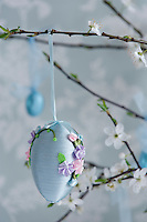 Detail of a beautifully made Easter egg decoration with tiny silk flowers hanging from a branch of cherry blossom