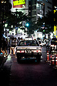 An older model Nissan Cedric of the Ebara Company plies the streets on a rainy night in Shibuya.
